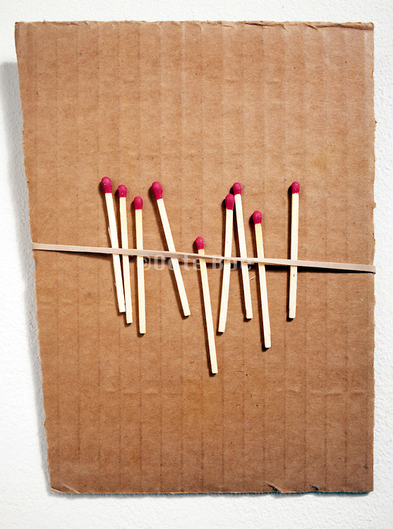 fire matches placed behind rubber string on piece of carton