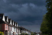 The dark skies of an approaching rain storm approach residential suburban homes in south London, on 24th May 2021, in London, England.