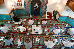 © Licensed to London News Pictures. 31/07/2020. London, UK. IMAM ISHAQ JASAT conducts prayers at Wightman Road Mosque, also known as London Islamic Cultural Society and Mosque, in north London as Muslims celebrate the festival of Eid. Last month the government announced that gatherings of more than 30 worshippers are allowed for acts of communal worship in churches, synagogues, mosques, temples and other places of worship. All worshippers attending Mosques for Eid celebrations have to wear face coverings and bring their own prayer mat, Quran, and a reusable shoe bag. Eid al-Adha, also called Eid Qurban or Bakra-Eid, is the second of two Islamic holidays celebrated worldwide each year, and considered the holier of the two. Photo credit: Dinendra Haria/LNP