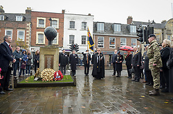 People stand at the war memorial during the remembrance service at Royal Wootton Bassett, Wiltshire.