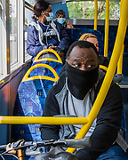 People travel on the bus, mostly masked, but only one seat apart - Passenger numbers are down dramatically on the tube and buses as people heed government guidance. Those who do travel obey the signs that are everywhere and many wear masks. The 'lockdown' continues for the Coronavirus (Covid 19) outbreak in London.