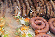 Italian sausages, peppers and onion cooking on a grill at a street festival in New York City.