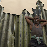 A worker rests on the tannery roof along side drying cowhides. Dharavi. August 2007