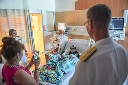 LOS ANGELES (Aug. 30, 2018) Rear Adm. Yancy Lindsey, commander of Navy Region Southwest and Lt. Emily Wilkin watch a patient take a photo wearing a female combination cover while visiting the Children's Hospital of Orange County during Los Angeles Fleet Week (LAFW).  LAFW is an opportunity for the American public to meet their Navy, Marine Corps and Coast Guard teams and experience America's sea services. During fleet week, service members participate in various community service events, showcase capabilities and equipment to the community, and enjoy the hospitality of Los Angeles and its surrounding areas. (U.S. Navy photo by Mass Communication Specialist 3rd Class Chanel L. Turner/Released) 180830-N-OI558-0340