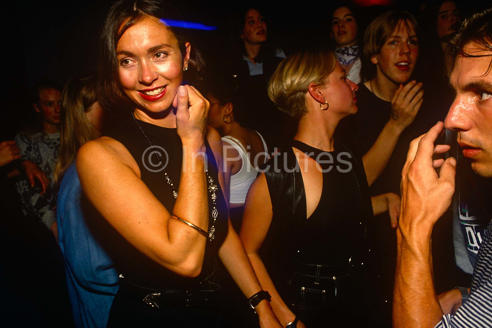 A beautiful brunette woman is watched by an unknown male in a club in London's West End during a packed Bhangra-themed music night. As if being stalked by this male pest, we see a moment in this young woman's evening as she enjoys a night out with girlfriends. The man scratches his nose at the same time as the woman brushes her hand against her cheek. It is hot in the busy club and the man is seen perspiring – he may be a stalker and he may be an innocent bystander – but it does look as though he has a keen interest in this dark-haired beauty. The Asian music is loud and the atmosphere is a pounding throng of young people but our attention is still with the two people, one oblivious to the other.