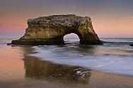 Arch rock and waves on sand beach in evening light, Santa Cruz, California