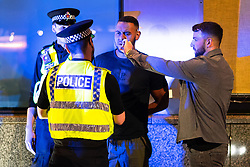 © Licensed to London News Pictures . 18/06/2021. Manchester, UK. Police cuff and detain a man (centre) as a second man holds a cigarette for the first , on Peter Street , following the European Cup tie between England and Scotland at Wembley Stadium . Photo credit: Joel Goodman/LNP