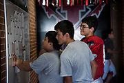 Members of the Iraan High School football team check the rooming list posted on the wall before practice in Iraan, Texas on December 13, 2016. (Cooper Neill for The New York Times)