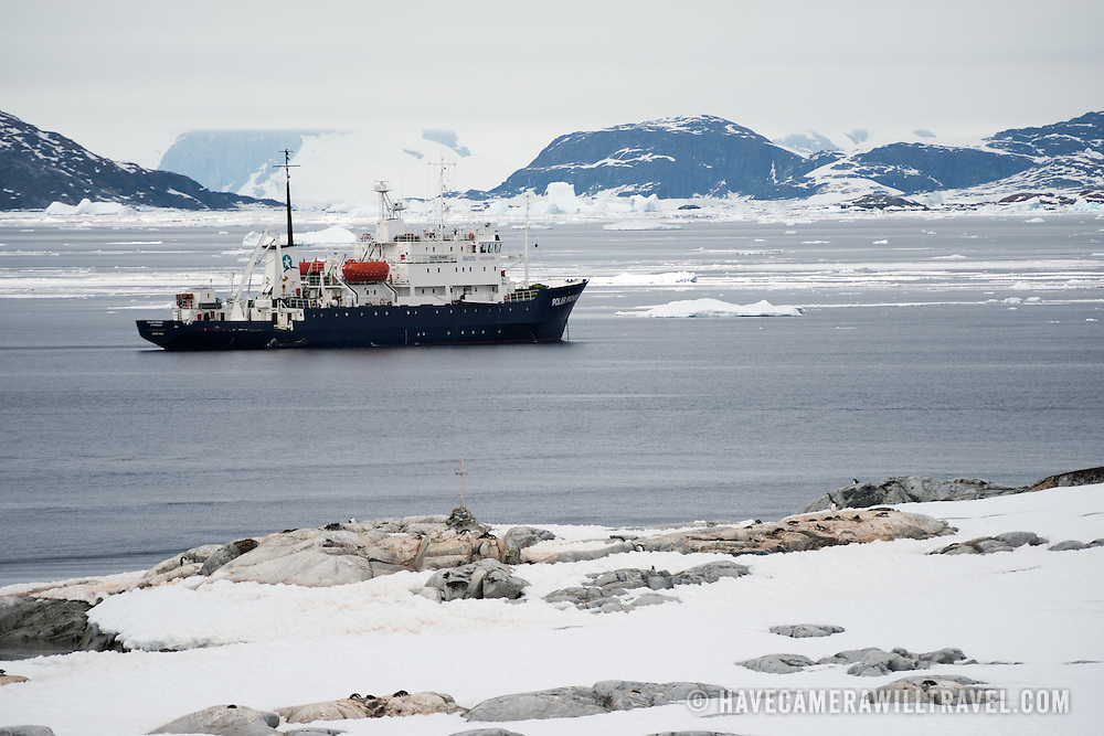 The Polar Pioneer, an Antarctic cruise vessel, is anchored off the shore of Petermann Island on the Antarctic Peninsula.