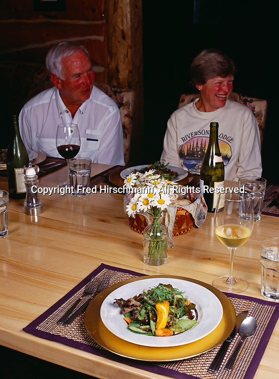 Fresh salad served at dinner table with guests Jack and Lee Hancock beyond, Winterlake Lodge, Finger Lake, Alaska.