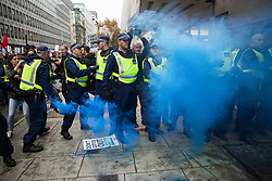 Metropolitan Police officers observe a smoke grenade let off by students attending a National Demonstration for a Free Education on 4th November 2015 in London, United Kingdom. The demonstration was organised by the National Campaign Against Fees and Cuts (NCAFC) in protest against tuition fees and the Government's plans to axe maintenance grants with effect from 2016.