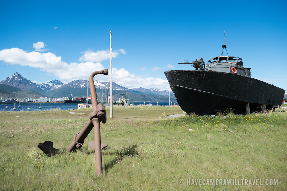 A PT boat, formerly of the Argentinian Navy, the Ara Towwora, sits on the shore of Ushuaia Harbor as a naval monument.