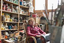 Female artist relaxing on her rocking chair in art studio, Bavaria, Germany