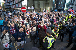 © Licensed to London News Pictures . 27/09/2018. London, UK. Protestors look up and cheer as former EDL leader Tommy Robinson (real name Stephen Yaxley-Lennon ) waves from inside the Old Bailey , where he faces a retrial for Contempt of Court following his actions outside Leeds Crown Court in May 2018 . Robinson was already serving a suspended sentence for the same offence when convicted in May and served time in jail as a consequence , but the newer conviction was quashed by the Court of Appeal and a retrial ordered . Photo credit: Peter Macdiarmid/LNP
