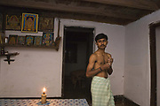 Indian man wearing a Lungi / Kaili with a Hindu shrine in the background. Coorg or Kadagu is the largest coffee growing region of India, in the state of Karnataka, the inhabitants - the Kodavas have been cultivating crops such as coffee, black pepper and cardamon for many generations.