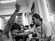 """07 MARCH 2015 - NAKHON CHAI SI, NAKHON PATHOM, THAILAND: A man channels the powers of his new tattoo at the Wat Bang Phra tattoo festival. Wat Bang Phra is the best known """"Sak Yant"""" tattoo temple in Thailand. It's located in Nakhon Pathom province, about 40 miles from Bangkok. The tattoos are given with hollow stainless steel needles and are thought to possess magical powers of protection. The tattoos, which are given by Buddhist monks, are popular with soldiers, policeman and gangsters, people who generally live in harm's way. The tattoo must be activated to remain powerful and the annual Wai Khru Ceremony (tattoo festival) at the temple draws thousands of devotees who come to the temple to activate or renew the tattoos. People go into trance like states and then assume the personality of their tattoo, so people with tiger tattoos assume the personality of a tiger, people with monkey tattoos take on the personality of a monkey and so on. In recent years the tattoo festival has become popular with tourists who make the trip to Nakorn Pathom province to see a side of """"exotic"""" Thailand.   PHOTO BY JACK KURTZ"""
