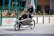 In Nijmegen fietst een vrouw met een andere vrouw in een tweewielige bakfiets door het centrum. Bakfietsen worden in heel Europa steeds vaker ingezet, zowel door particulieren als bedrijven. Het is een duurzame vorm van transport en biedt veel voordelen.<br /> <br /> In Nijmegen a woman cycles with another woman in the two-wheel cargo bike in the city center. Cargo bikes are increasingly being deployed across Europe, both individuals and businesses. It is a sustainable form of transport and offers many advantages.