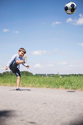Small boy playing football on road in the countryside, Bavaria, Germany