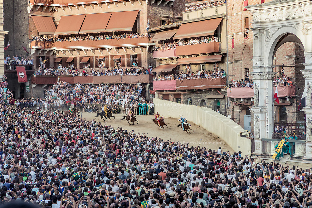 """Italy, Siena, the Palio: san Martino curveOn the basis of a detailed reconstruction of horse accidents which have happened on this race-track during the last 20 years of the Palio, we see that the greatest number of accidents have happened at San Martino (57% of the cases) in respect to """"Casato"""" (37% of the cases.)<br /> <br /> But while at the curve at San Martino the accidents have happened both on the first lap (45%) as well as on the second lap (55%), at the """"Casato"""" curve the accidents have happened mostly on the first lap (70%). In the past the borders of this curve were covered in mattresses in an attempt to protect falling horses and jockeys. Recently, however, the curve is sheathed in the same plastic material used as buffer in car racing. At the shot of the mortaretto, the horses come out of the Entrone and line up at the starting line, known as the mossa. As soon as the last horse reaches the starting line the race begins and lasts for three rounds of the square (about 1 kilometre in total). The first horse to cross the finishing line is the winner, regardless of whether it is still mounted."""