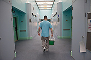 An enhanced prisoner returns the mop and bucket to the stores cupboard after cleaning his cell floor on H wing at YOI Aylesbury.