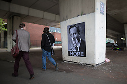 """© Licensed to London News Pictures . 23/05/2015 . Manchester , UK . A poster featuring an image of David Cameron burning cash , with the caption """" HOPE """" , pasted in an underpass in central Manchester . Photo credit : Joel Goodman/LNP"""