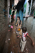 Dhaka, Bangladesh. Life in Mirpur, Shahnaz leading the way to a  garment factory through back alleys.The Stars Foundation visiting CSID.<br /> Centre for Services and Information on Disability (CSID) is a charity working for integrating disabled children into mainstream society.