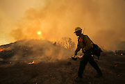 A firefighter walks by the wildfire near Placenta Canyon Road in Santa Clarita, Calif., Sunday, July 24, 2016.(AP Photo/Ringo H.W. Chiu)