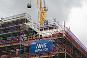 A sign reading 'NHS Thank You' is displayed on scaffolding around a construction site on 1st July 2020 in Windsor, United Kingdom. People around the UK will applaud NHS workers on the 72nd birthday of the National Health Service on 5th July.