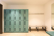Dressing room with turquoise lockers. Benches to change outfit. Nobody inside