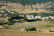 Agricultural scene farmer spraying with tractor by village of Ollo in Sierra de Andia in Biskaia Basque region of Northern Spain