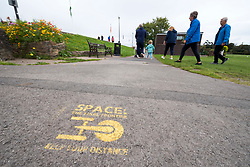 "© Licensed to London News Pictures; 09/09/2020; Clevedon, UK. Stencils are seen on the pathways by the Marine Lake advising people to keep social distancing during the coronavirus covid-19 pandemic. North Somerset has the highest infection rate in the South West of England. The stencils by North Somerset Council with their logo refer to cultural memes such as Star Trek ""Space the final frontier"", the film Alien ""In Space no one can hear you sneeze"", the song ""Don't Stand So Close To Me"" by the Police and the world war one recruitment poster ""North Somerset needs you to keep your distance"". Other stencils have been added referring to the climate crisis and global warming. Photo credit: Simon Chapman/LNP."