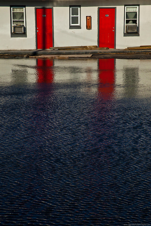 Due to clogged storm drains these red doors are reflected in the flooded parking lot of a West Atlantic City Motel.