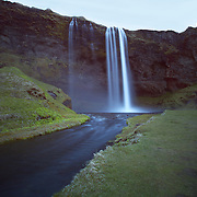 Seljalandsfoss is one of Iceland's famous waterfalls. Water from the river Seljalandsá drops 60 metres (200 ft) over the cliffs of the former coastline. There is  a foot path behind it at the bottom of the cliff. It is the only known waterfall of its kind in Iceland, where it is possible to walk behind it.