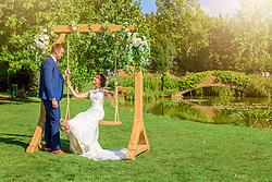 Bride on swing smiling at Groom