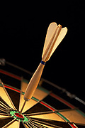 Close up dramatically lit photo of a dart in the bullseye of a dartboard