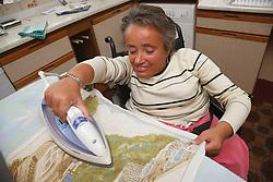 Wheelchair user with Spina Bifida ironing in her kitchen