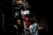 A woman labourer is carrying a bag of cement on her head while children are playing along the narrow shady passageways of the slum next to the train station of Bandra (East), Mumbai, India, where famous child actors Azharuddin Ismail and Rubina Ali, playing the roles of 'young Salim' and 'young Latika' in the movie Slumdog Millionaire, winner of 8 Oscar Academy Awards in December 2008, still live with their families. Various promises were made to lift the two young actors from poverty and slum-life but as of the end of May 2009 anything is yet to happen. Rubina's house was recently demolished with no notice as it lay on land owned by the Maharashtra train authorities and she is now permanently living with her uncle's family in a home a stone-throw away in the same slum. Azharuddin's home too was demolished in the past two weeks, as it happens every year in his case, because the concrete walls were preventing local authorities to clear a drain passing right behind it. As usual, his father is looking into restoring the walls as soon as the work on the drain has been completed.