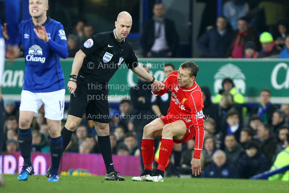 Lucas Leiva of Liverpool is helped up by referee Anthony Taylor. Barclays Premier league match, Everton v Liverpool at Goodison Park in Liverpool, Merseyside on Saturday 7th February 2015<br /> pic by Chris Stading, Andrew Orchard sports photography.