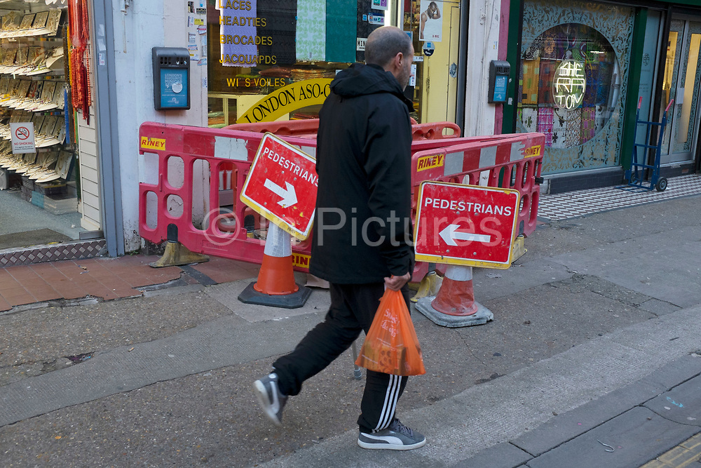Two pedestrian signs pointing in opposite directions. London, UK.