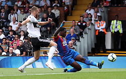 Crystal Palace's Jeffrey Schlupp (right) scores his side's first goal of the game during the Premier League match at Craven Cottage, London.
