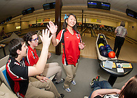 Trevor Lange and Zina LaBrie give a high five to Lily Chanthasak during the Baker Match against the LHS Faculty at Funspot on Thursday afternoon.  (Karen Bobotas/for the Laconia Daily Sun)