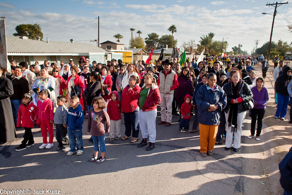"""Dec. 12, 2009 -- PHOENIX, AZ: People walk through the street during a procession to honor the Virgin of Guadalupe at St. Catherine of Siena Catholic Church in Phoenix, AZ. Most of the members of the church are Hispanic and Dec. 12, Virgin of Guadalupe Day, is one of the church's most important holy days. The Virgin of Guadalupe appeared to Juan Diego, a Mexican peasant, on Dec 9, 1531, on a hillside near Mexico City. She is the """"Queen of Mexico"""" and """"Empress of the Americas"""" and revered throughout Latin America.  Photo by Jack Kurtz"""