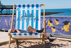 © Licenced to London News Pictures <br /> <br /> 24 June 2018 . Aberystwyth Wales UK<br /> <br /> UK Weather:  A man relaxes in a giant deckchair at the seaside  in Aberystwyth on yet another scorchingly hot  and sunny day, as the UK heads into a mini heatwave, with temperatures forecast to hit 29º or 30º Celsius by the middle of the week<br /> <br /> photo credit :Keith Morris / LNP