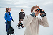 Robin de Vries (hiking with Sofie Vej Ugelvig, left, and Alexander Lohse) looks through his binoculars on a hike across Sverdruphamaren, Svalbard.