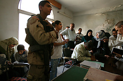 U.S. soldier Juan Arevalo, 20, waits with translator Alyaa Abdul Hassan Abbood, 23, as Iraqi civilians crowd into the courtroom to receive monetary compensation for damages done by American troops in Baghdad, Iraq, Sept. 27, 2003.