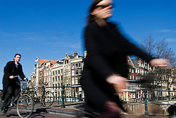 Cyclists riding through street in Amsterdam Netherlands