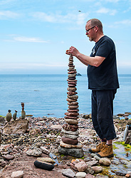Dunbar, East Lothian, Scotland, United Kingdom 10 July 2021. European Stone Stacking Championship: The first day of the event, which is part of the Edinburgh Science Festival.  Pictured: Neil Andrews competes in the most stones stacked in half an hour competition. His tower comprising 37 stones was the winning stack. The record is 42.<br /> Sally Anderson | EdinburghElitemedia.co.uk
