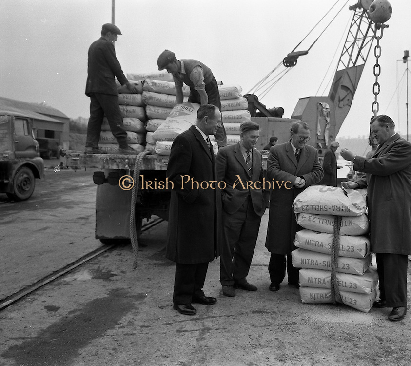 """11/02/1963<br /> 02/11/1963<br /> 11 February 1963<br /> Nitra-Shell 23 cargo discharged at New Ross, Co. Wexford. The """"M.V. Roelf Buisman"""" from Rotterdam on it's first visit to New Ross delivering 500 ton of Nitra -Shell 23 the first consignment of 23% Nitrogen imported into Ireland. Messrs. Albatross Windmill Fertiliser Co. Ltd. were the importers. Picture shows Mr. E.F. Storey, Managing Director, Albatross Windmill Fertiliser Co. Ltd. (right), looking at some of the Nitra-Shell 23 along with (l-r): Mr. M. Murphy, Manager J.J. Stafford (New Ross); Captain  Smith of the """"Roelf Buisman"""" and Mr. J.J. Boyle, General Manager of Shell and Albatross (Agricultural) Ltd."""
