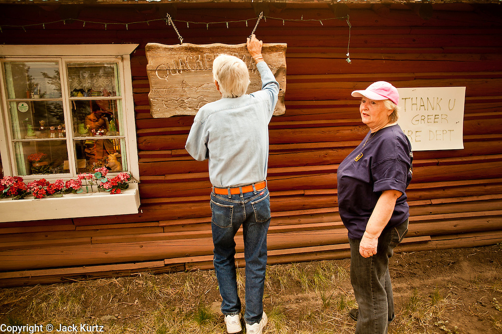 """05 JUNE 2011 - GREER, AZ:  Bob Cline (CQ) and his wife, Judy Cline (CQ) take down the sign at their business in Greer, the """"Quacker Barrel"""" (CQ QUACKER). The business has been in their family since 1954 and this is the first time they've had to close and evacuate. The fire grew to more than 180,000 acres by Sunday with zero containment. A """"Type I"""" incident command team has taken command of the fire.    PHOTO BY JACK KURTZ"""