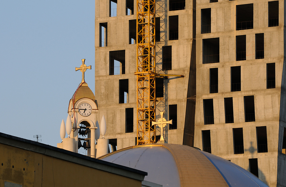 The bell and clock tower of the Resurrection of Christ Orthodox Cathedral of Tirana beside a new high rise building . Triana, Albania